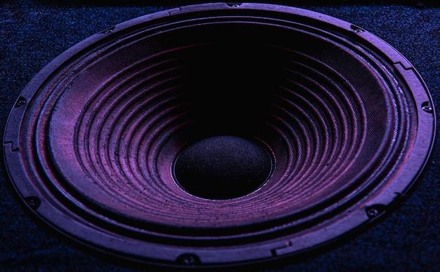 Close-up van luidsprekermembraan op zwarte achtergrond met gekleurde verlichting.