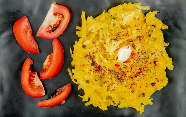 Close-up van macaroni pasta en gesneden tomaat in plaat