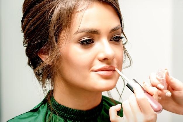 Close up van make-up artiest lippenstift foundation met een make-up borstel toe te passen