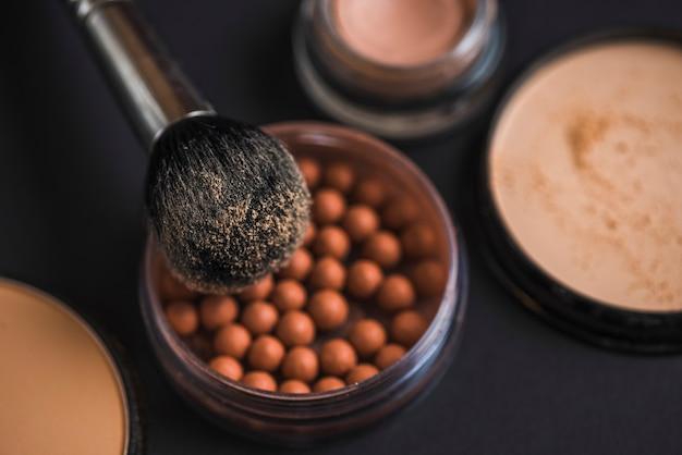 Close-up van make-upborstel op bronzende parels