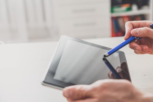 Close-up van man aan het werk met stylus op digitale tablet pc.