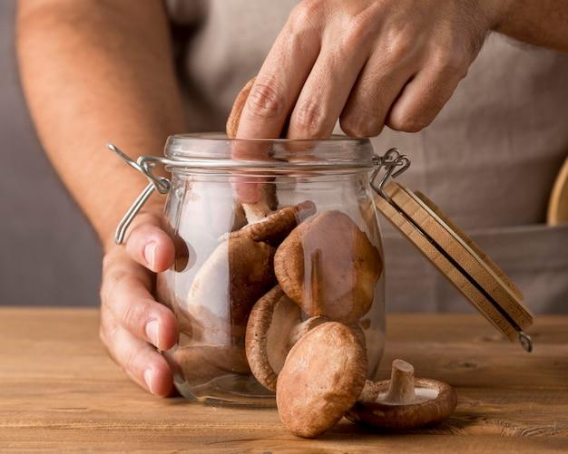 Close-up van man champignons aanbrengend glazen pot