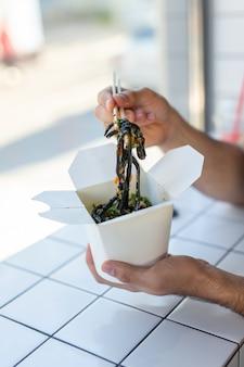 Close-up van man chinese noedels eten in een café het concept van gezonde aziatische keuken