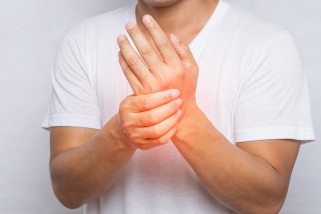 Close up van man die lijdt aan pijn in de hand of pols