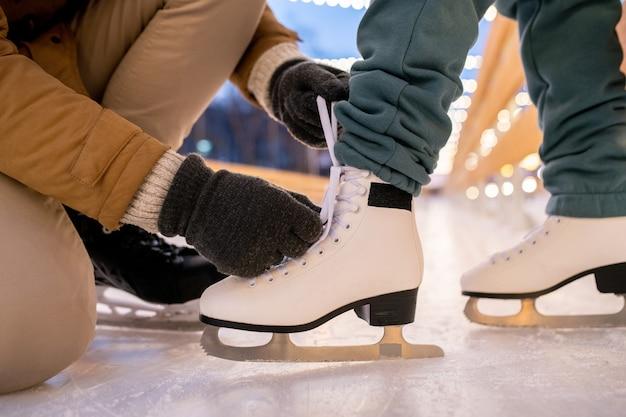 Close-up van man die schoenveter op schaatsen van zijn vriendin bindt terwijl ze op de ijsbaan staan