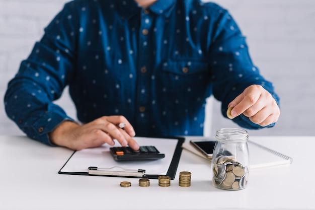 Close-up van man die winst berekenen die calculator op witte lijst gebruiken