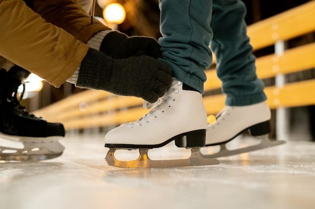 Close-up van man die zijn vriendin helpt schoenveters op kunstschaatsen te strikken voordat ze gaan schaatsen