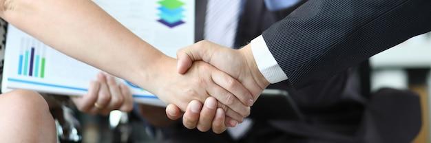 Close-up van man en vrouw handen schudden voor lachende man met documenten. zakelijke deals concept uitvoeren.