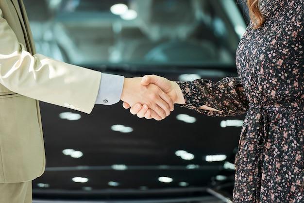 Close-up van man en vrouw staan en elkaar handen schudden na deal in auto salon