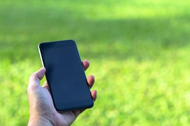 Close-up van man hand die en slimme telefoon met het lege scherm op openluchtpark houdt met behulp van