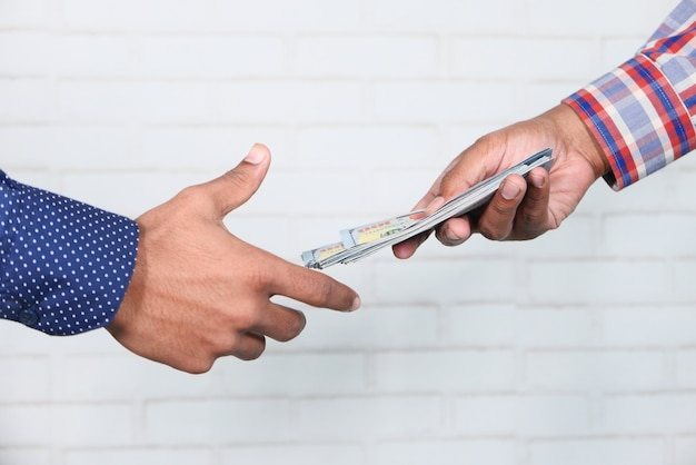 Close-up van man hand geven ons dollar contant geld.
