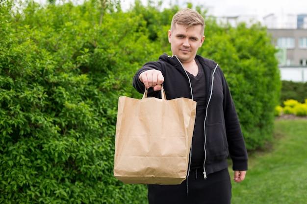 Close up van man hand met eco papieren zak voor afhaalmaaltijden op natuur groene achtergrond. levering in alle weersomstandigheden de klok rond aan de klant.
