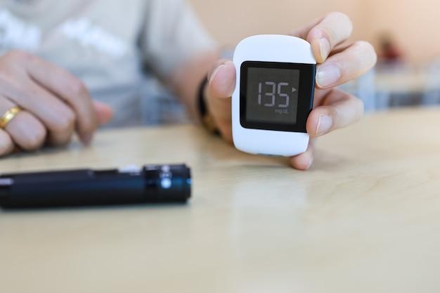Close up van man hand met glucosemeter met lancet