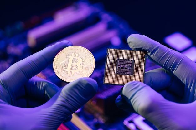 Close-up van man handen in handschoenen houden gouden bitcoin en cpu op moederbord