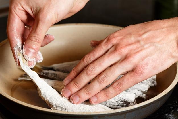 Close-up van man handen zetten de verse vis smelt in bloem op koekenpan. ongezond eten op olie