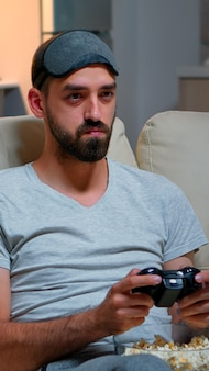 Close-up van man met oogslaapmasker die videogames speelt met joystick