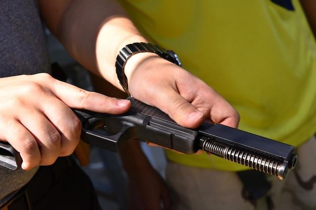 Close up van man monteren ontmantelen onderhoud pistool deel op veiligheidszone op schietbaan
