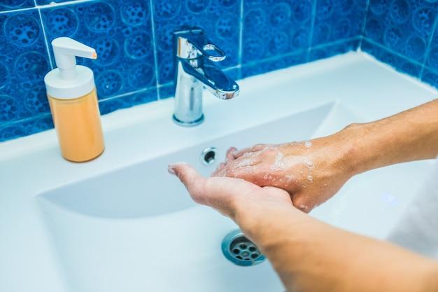 Close-up van man of vrouw thuis in de badkamer die voorkomt dat coronavirus of covid-19 zijn handen wassen en reinigen met water en zeep - regels om virussen te voorkomen - quarantaine en lockdown-levensstijl
