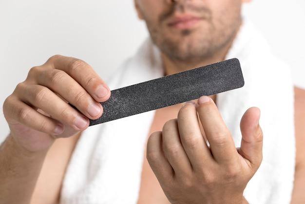 Close-up van man's hand polijsten zijn nagel met boete