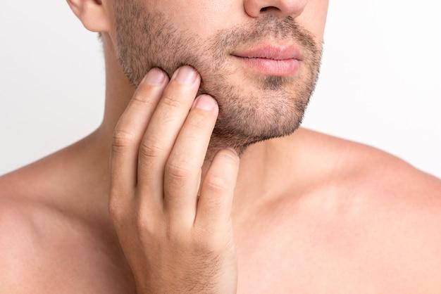Close-up van man's hand wat betreft zijn gezicht