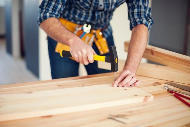Close up van man spijker door hamer te raken