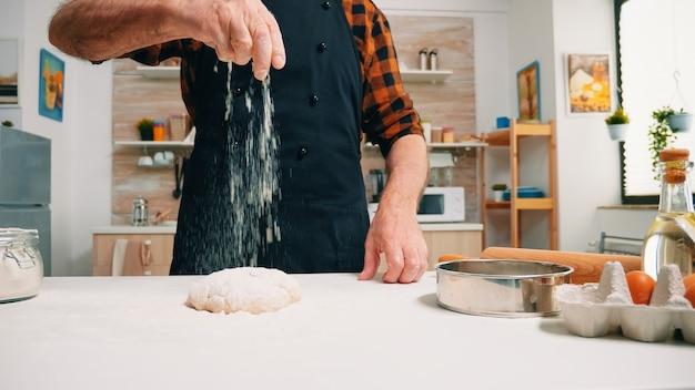 Close up van man zeven bloem op brooddeeg op houten tafel in de keuken. oudere senior bakker met bonete en uniform besprenkelen, zeven, nieuwe ingrediënten op deeg verspreiden, zelfgemaakte pizza bakken