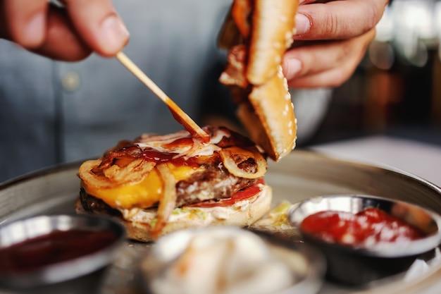 Close-up van man zit in restaurant en mayo aanbrengend hamburger.