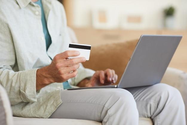 Close-up van man zittend op de bank met laptop op zijn knieën hij online winkelen met creditcard