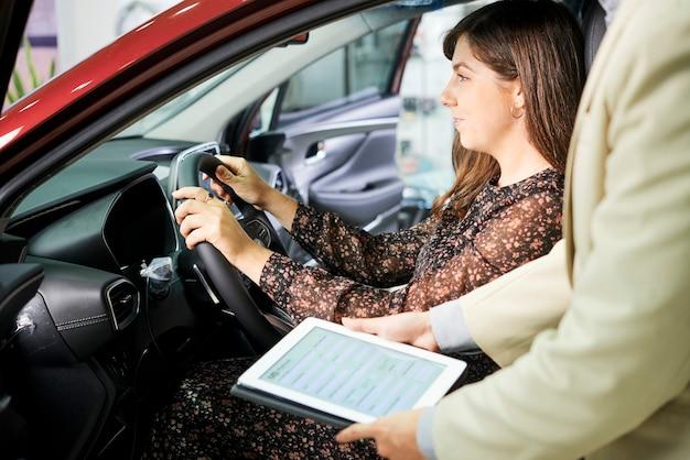 Close-up van manager van autosalon die zich met tabletpc bevindt en aan vrouwelijke klant voorstelt om haar nieuwe auto te verzekeren