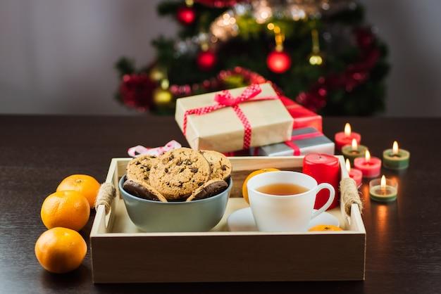 Close-up van mandarijnen, kaarsen, chocoladekoekjes, thee en geschenken met kerstboom op