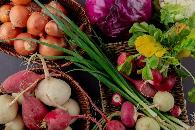 Close-up van manden en plaat van groenten als ui radijs lente-ui en kool op kastanjebruine achtergrond