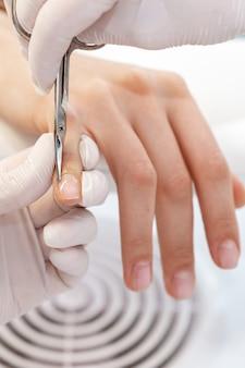 Close-up van manicure met manicure schaar om cuticula van vrouwelijke nagels in manicuresalon te verwijderen