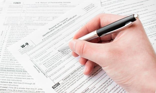 Close up van mannelijke accountant belastingformulier invullen. man schrijven iets zittend op zijn kantoor.