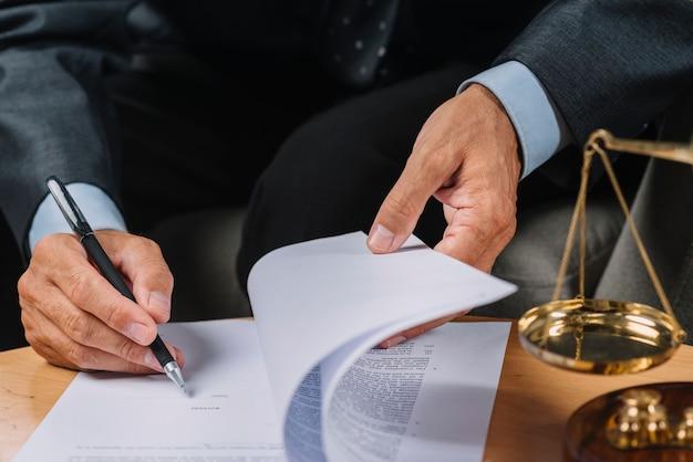 Close-up van mannelijke advocaat die het contractdocument op het bureau ondertekent