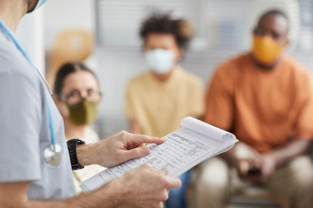 Close-up van mannelijke arts die klembord vasthoudt terwijl hij praat met patiënten die in de rij staan in de medische kliniek, kopieer ruimte