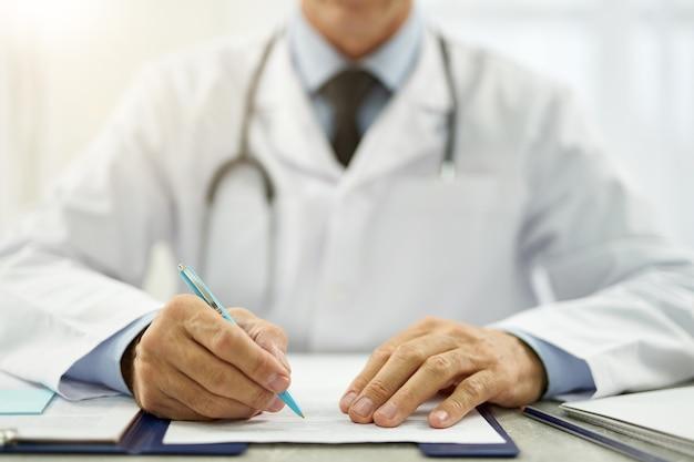 Close-up van mannelijke arts in laboratoriumjas die aan tafel zit en papierwerk doet in de kliniek