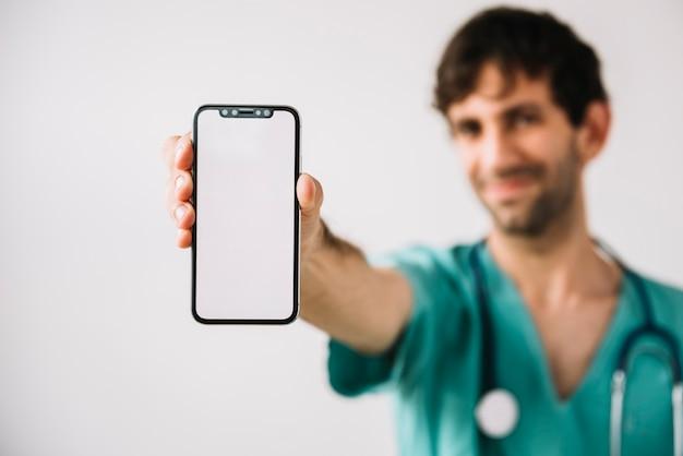 Close-up van mannelijke artsenhand die mobiele telefoon met behulp van
