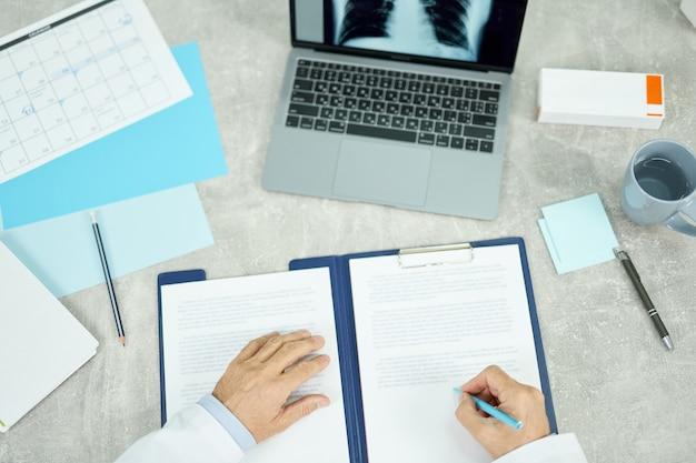 Close-up van mannelijke artsenhanden die papierwerk doen terwijl de man aan tafel zit met een notitieboekje, papieren en kopje koffie and