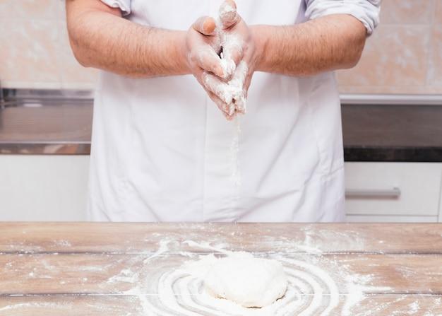 Close-up van mannelijke bakker die de bloem op gekneed deeg over de houten lijst bestrooien