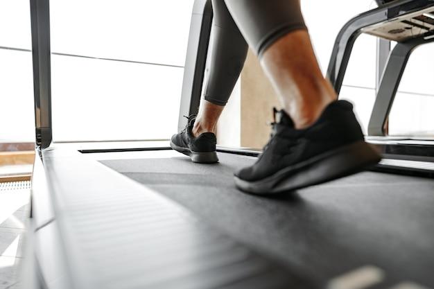 Close up van mannelijke benen lopen in een sportschool op een loopband
