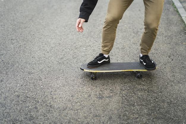 Close-up van mannelijke benen op een schaats op asfalt