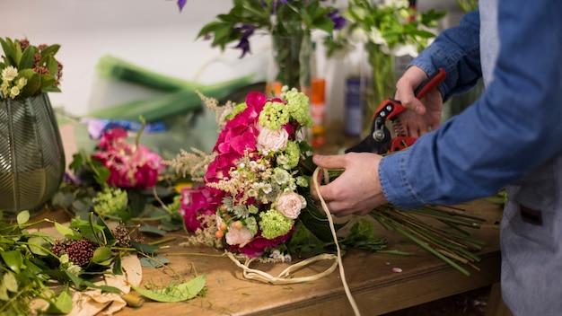 Close-up van mannelijke bloemist die bloemboeket in de bloemwinkel creëren
