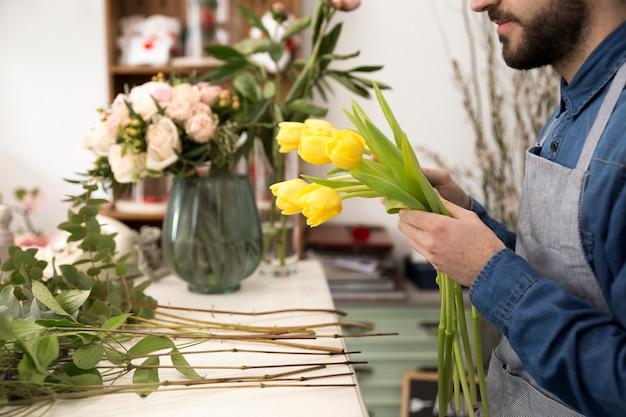 Close-up van mannelijke bloemist die de gele tulpen in de bloemwinkel schikken
