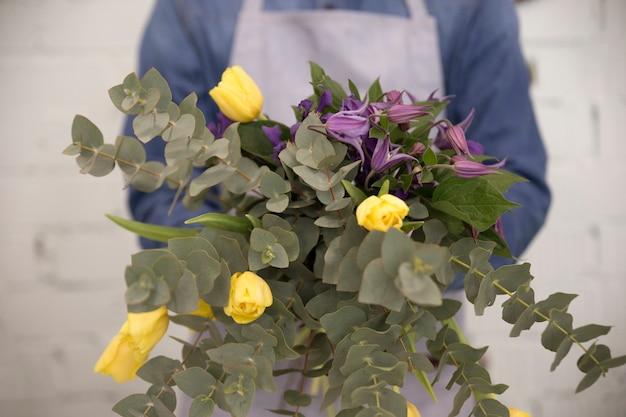 Close-up van mannelijke bloemist die mooi bloemboeket in hand toont