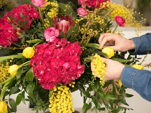 Close-up van mannelijke bloemisthand die de bloemen in de vaas schikken