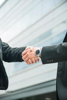Close-up van mannelijke en vrouwelijke handen schudden op zakelijke deal