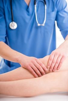 Close-up van mannelijke fysiotherapeut die been masseren.