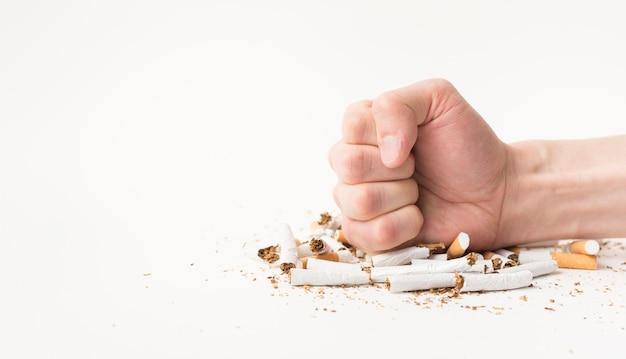 Close-up van mannelijke hand brekende sigaretten met zijn vuist
