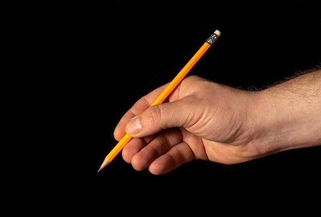 Close-up van mannelijke hand met potlood op geïsoleerde zwarte achtergrond