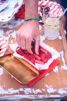 Close-up van mannelijke hand plukken rode snoep van een doos met limonadeglas en fluitje van een cent in een zomerfeest summer